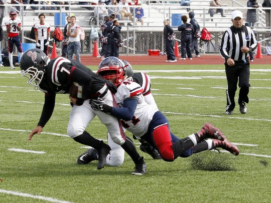 Elmira's Max Temple is dragged down by Binghamton's Fendi Deadwyler on Saturday at Ernie Davis Academy.