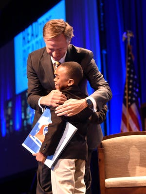 Gov. Bill Haslam hugs John Little IV during an event announcing a new statewide reading initiative Wednesday at Music City Center.