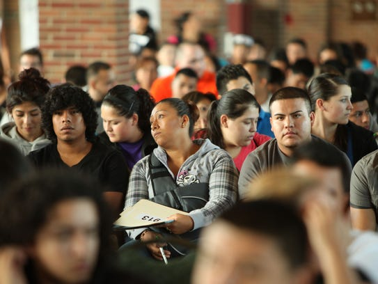 Undocumented immigrants wait to fill out applications