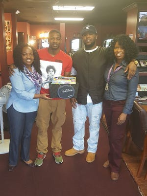Javis Rhodes, middle, receives his first book box from the Fade2Read founders, Samantha Boyd, far left, and Shiree Fowler, far right. Also pictured: Barber Tristan Jackson.
