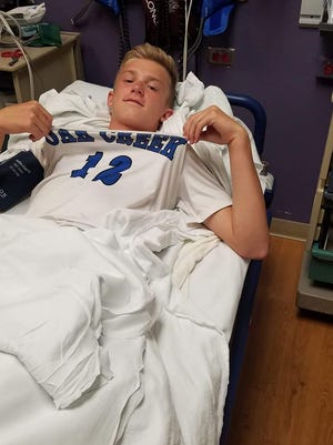 Cayden Carlson holds up his jersey in the hospital room after getting transported by ambulance on Aug. 24. The Knights junior broke his pelvis in a win over Racine St. Catherine's.