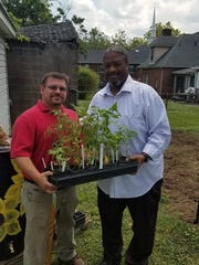Vito Sagliano, Republican candidate for the U.S. House of Representatives, donates plants for the community garden. He's shown with the Rev. Chris Battle.