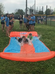 Members of the Airline softball team slip and slide with Emilie Gibson Monday afternoon.