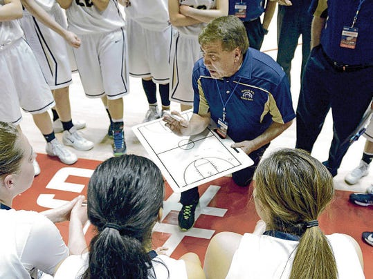 Former Santa Fe High head girls basketball coach Elmer Chavez coaches his team during a time-out during the third quarter of the Class 4A semifinal game March 13, 2014, at The Pit in Albuquerque.