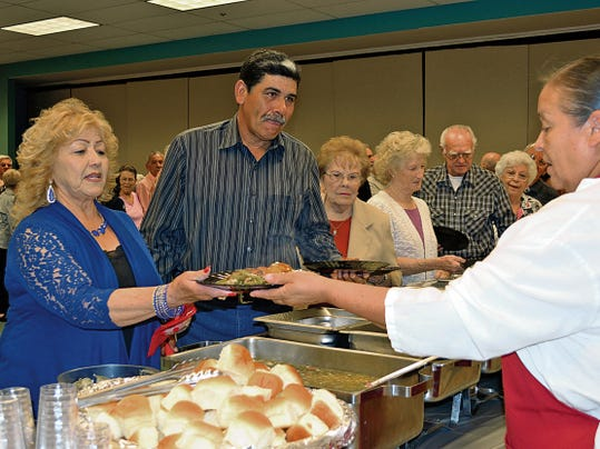 Elena Ruiz - Headlight Photo   Elvira Garcia, a Deming Senior Center volunteer, is served her dinner plate Friday evening at the 2015 Volunteer Recognition Awards hosted by the Deming-Luna County Commission on Aging at the Special Events Center.
