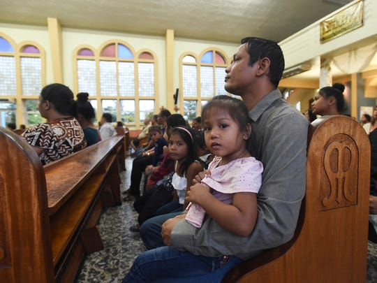Thomas Duenas, 34, the brother of Melinda Sue Duenas, 32, who died Sunday morning after being struck by a Jeep, holds his daughter Tara, 2, during a rosary Mass at the Our Lady of Lourdes Church in Yigo on June 4, 2018.