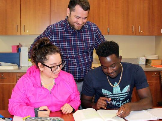 Dr. Mark Heimermann works with students Esmeralda Garcia and Wisner Fleurjean.