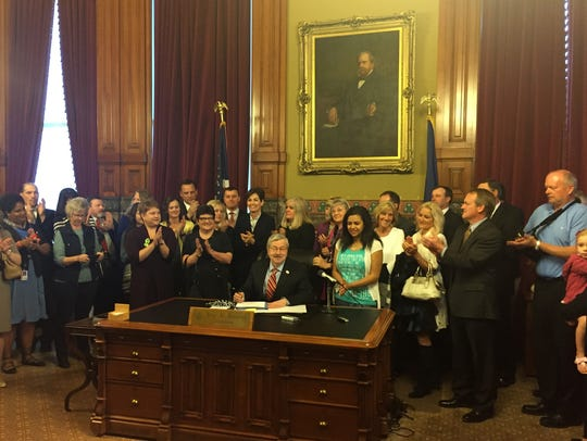 Supporters applaud Friday, May 5, 2017, as Gov. Terry