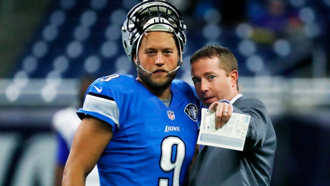 Lions quarterback Matthew Stafford talks with team executive vice president & general manager Bob Quinn before an NFL preseason game against the Buffalo Bills on Sept. 1, 2016, in Detroit.