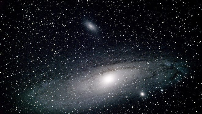 The Andromeda Galaxy, M31. The bright spot along its lower edge is satellite galaxy M32; above M31 as seen here is its satellite, M110. A small telescope will show the satellites. [Photo by Parker Bossier (Own work) [CC BY-SA 4 (https://creativecommons.org/licenses/by-sa/4)], via Wikimedia Commons]