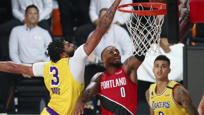 Los Angeles Lakers forward Anthony Davis (3) blocks a shot by Portland Trail Blazers guard Damian Lillard (0) as Lakers forward Kyle Kuzma (0) looks on during Game 2 of an NBA first-round playoff series Thursday night in Lake Buena Vista, Fla. Game 3 is scheduled for Saturday night.