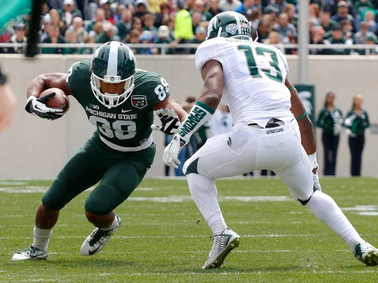 Michigan State Green team's Monty Madaris, left, runs on a pass reception against the White team's Vayante Copeland (13) during the Spartans' spring NCAA college football game, Saturday, April 25, 2015, in East Lansing, Mich. The White team won 9-3.