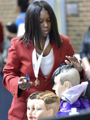 Cosmetology student Cydneedru Jackson, 17, of Detroit, styles hair on mannequins prior to a March 25, 2018 news conference at the Breithaupt Career and Technical School to announce revitalization efforts for the center.