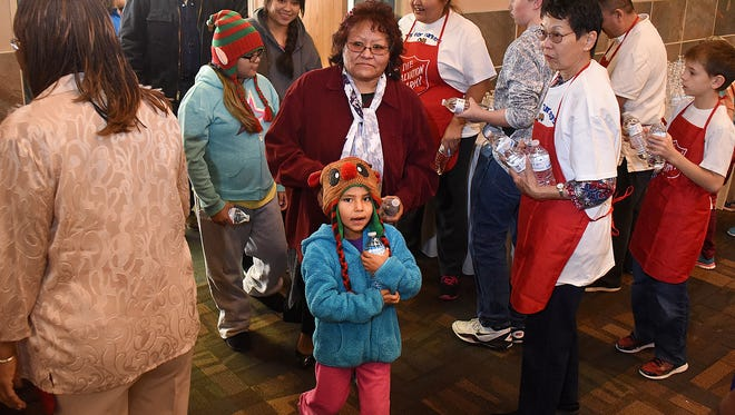 Alaina Vicenti, center, and Sabree Yazzie, 5, arrive on Thursday to the Farmington Civic Center for a community Thanksgiving meal.