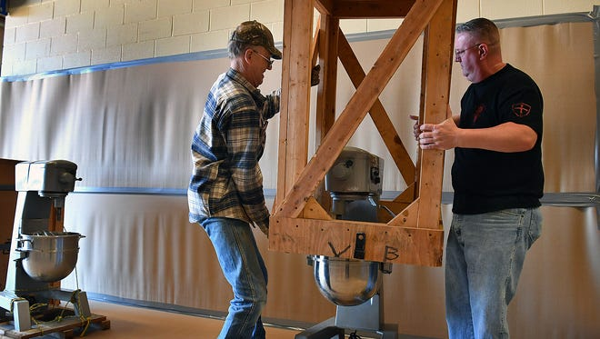 John Rhoads, left, and Scott Ermis of the University Kiwanis Club un-crate one of the commercial mixers that will make batter for the 62nd Annual Kiwanis Pancake Festival. The all-you-can-eat event kicks off Saturday morning at 6 a.m. and goes until 6 p.m. at the Bridwell Ag Center.