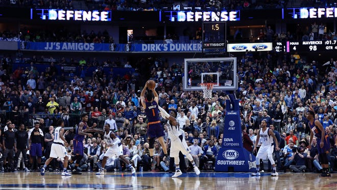 Mar 11, 2017; Dallas, TX, USA; Phoenix Suns guard Devin Booker (1) hits the game winning shot over Dallas Mavericks guard Wesley Matthews (23) during the fourth quarter at American Airlines Center.
