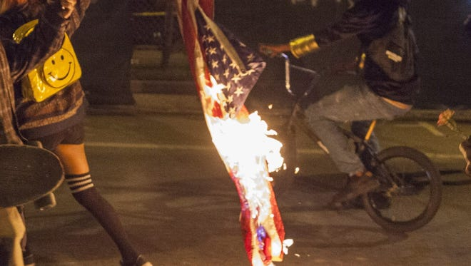 A demonstrator drags a burning  U.S. flag to protest  President-elect Donald Trump in Oakland. in November.