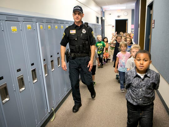 Seth Pionke, the police liaison officer for Plover-Whiting Elementary, leads students down the hall for a milk break, Wednesday, Sept. 23, 2015.