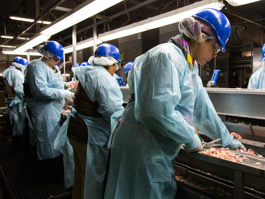Workers trim fat from chicken leg meat at the Allen Harim processing plant in Harbeson in this file photo.