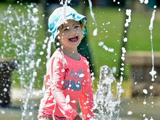 Three-year-old Rylie Rotz cools off on a hot Monday