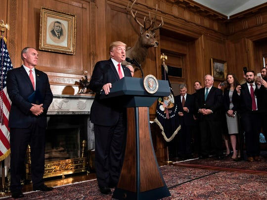 US Secretary of the Interior Ryan Zinke (L) listens while US President Donald Trump speaks before signing an executive order to review the Antiquities Act at the US Department of the Interior April 26, 2017 in Washington, DC.