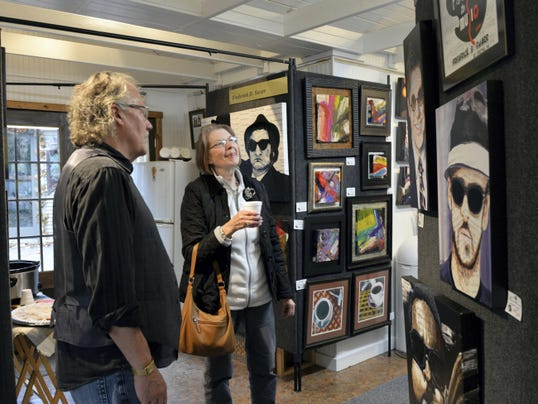 Cele Miller of Hershey admires the paintings of Mt. Gretna artist Fredrick Swarr in his Mt. Gretna gallery on Saturday during the Lebanon Valley Art Studio Tour.