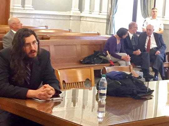 Michael Rotondo, left, sits during an eviction proceeding