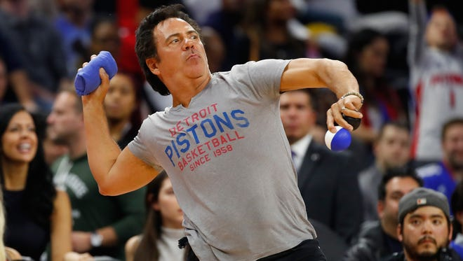 Pistons owner Tom Gores throws T-shirts into the stands during the Pistons' 108-82 win Friday at the Palace.
