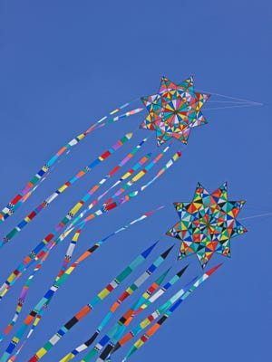 Multi-coloured kites in flight in a strong wind.