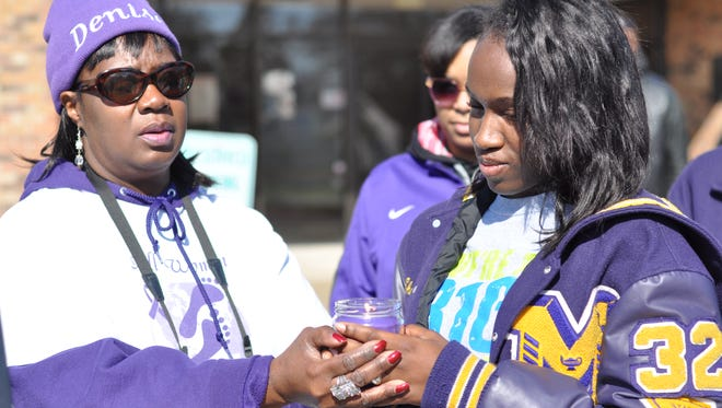 Denise Wolford (left), founder of All Women Marching for Hope, and Jasmine Williams light a candle Saturday for Laura Johnson Williams, a Marksville woman who was stabbed to death by her husband.