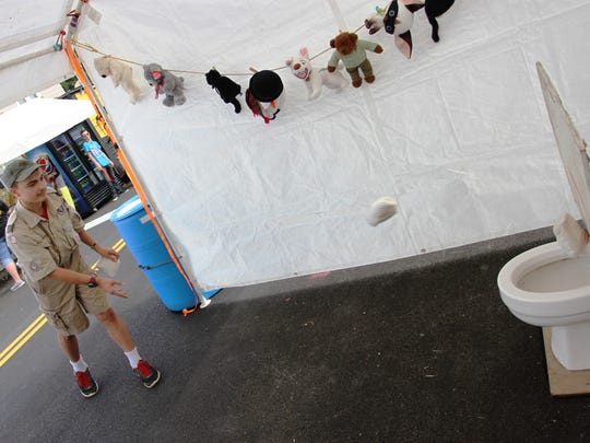 Pataskala Boy Scout Troop 21 member James Gauthier demonstrates the troop's toilet bowl toss game at the Pataskala Street Fair. Groups and organizations like Boy Scout Troop 21 remain a vital part of the annual four-day event.