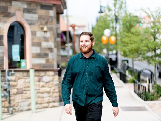 Ryan Wilusz, Knoxville News Sentinel urban life writer, walks past The Half Barrel in Knoxville, Tennessee on Wednesday, May 23, 2018.