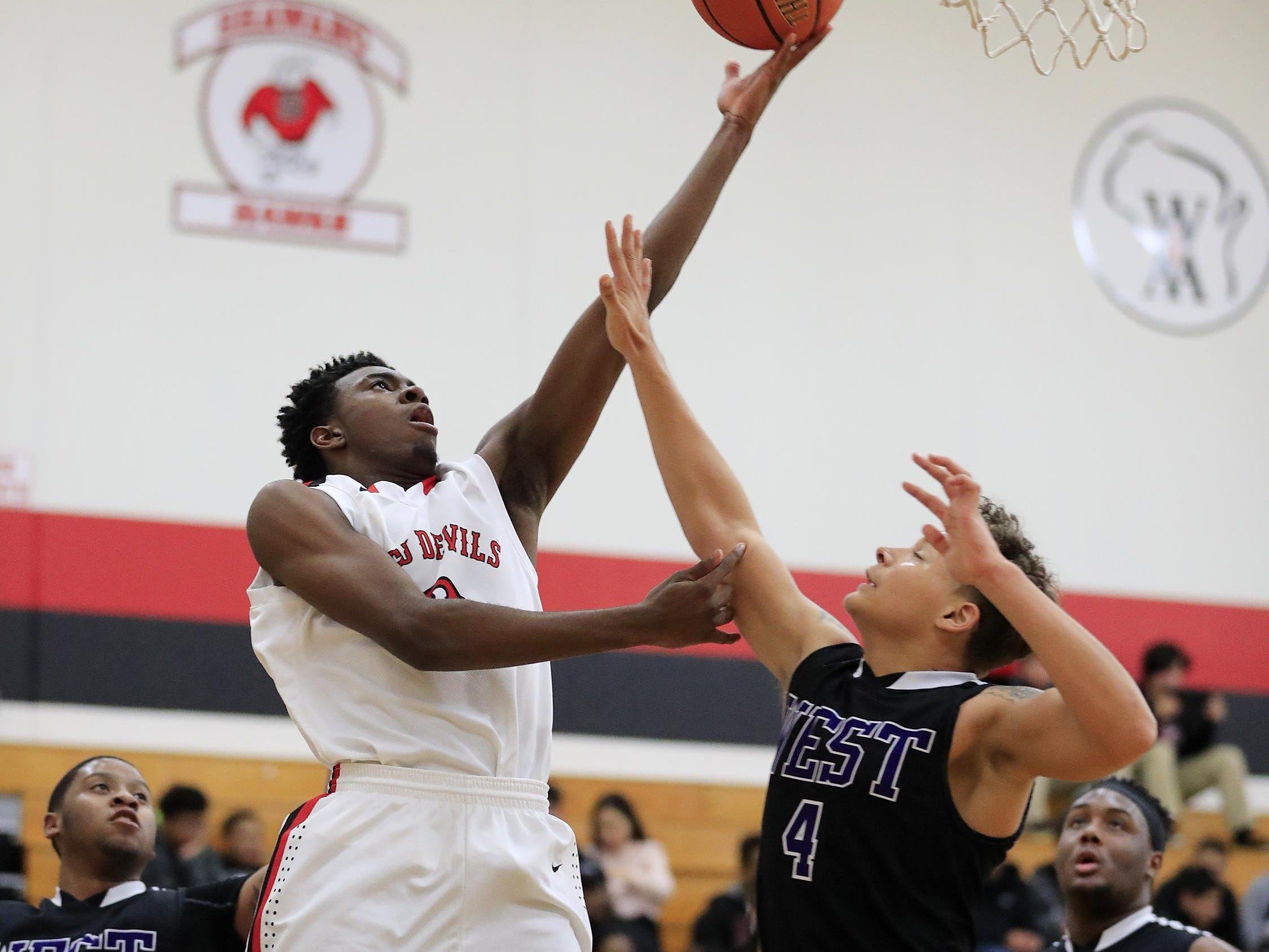 Green Bay East's Zack Crockett (2) scores a basket past Green Bay West's Brandon Dudley (4) in a Bay Conference boys basketball game on Jan. 3. Crockett averaged 18.1 points per game to finish as the Bay's second-leading scorer this season.