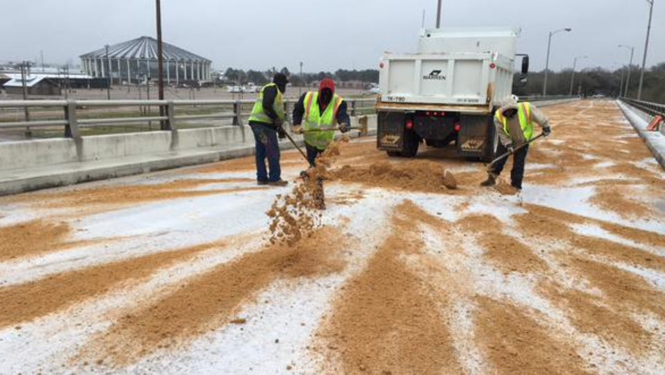 Jackson road crews apply a layer of sand to the Pearl