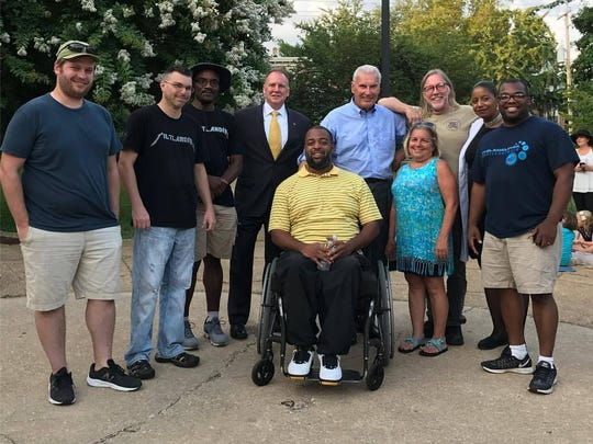 """Rob Pfeiffer (third from right) with his arm on Mayor Michael Purzycki, surrounded by fellow residents of """"Tiltlandia."""""""