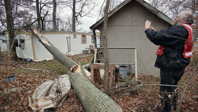 A representative from the American Red Cross takes photos of the scene where a downed tree damaged a home in Madison Township.