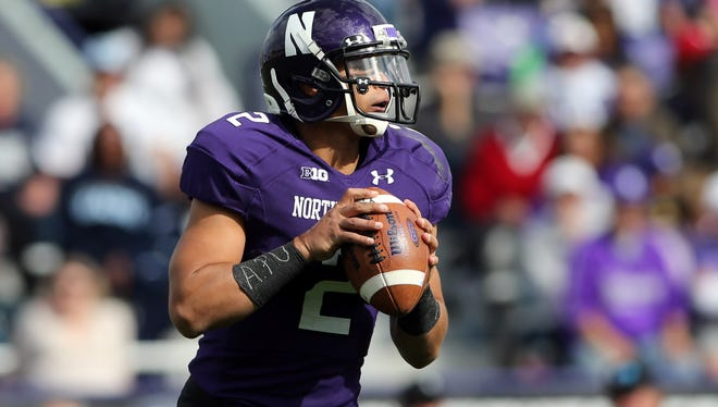 Northwestern quarterback Kain Colter (2) sets up to throw a pass while wearing a wristband with the phrase APU written on it during the game against Maine on Sept. 21 at Ryan Field in Evanston, Ill.