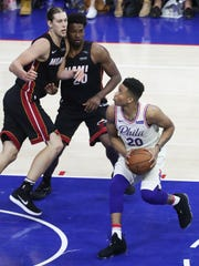 Philadelphia's Markelle Fultz looks to the basket past Miami's Kelly Olynyk (left) and Justice Winslow in the second half of the Sixers' 130-103 win in the opening game of the first round of the NBA playoffs at the Wells Fargo Center Saturday.