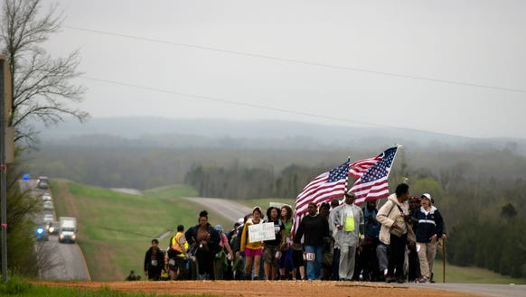 Marchers walk on Highway 80 while participating in