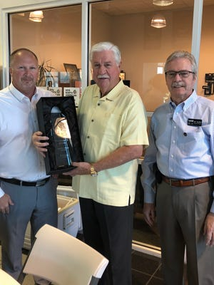 From left to right: district sales manager Dustin Townsend, owner Stephen Wade and general manager D.C. Moffitt celebrate with the 2018 President's Award trophy for Stephen Wade Honda