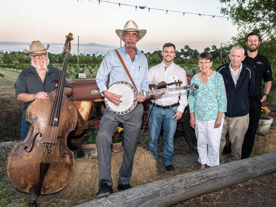 Blue Cypress Bluegrass members bass player Alan Rudd, banjo player Bill Hare, and fiddler Tom Callino with Schacht Groves owners Janet and Henry Schacht and Travis Beckett, owner of Wild Thyme Catering.