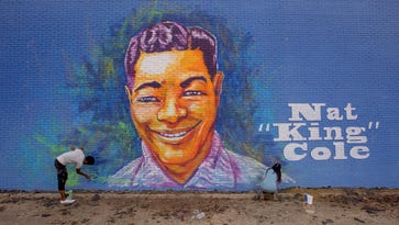 Artists Sunny Paulk and Corey Spearman put finishing touches on a mural of Nat King Cole on the side of a building in downtown Montgomery, Ala.