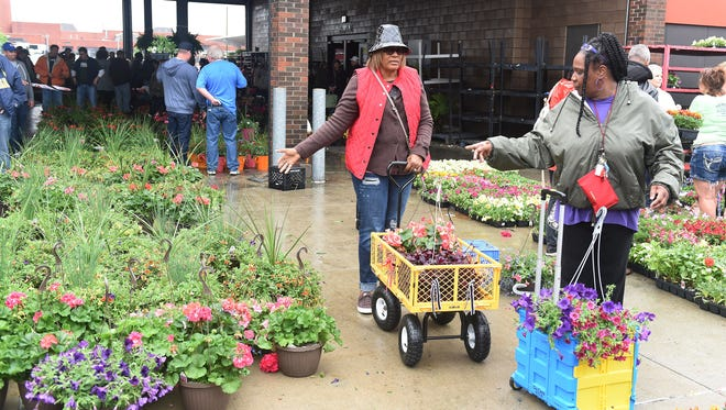 Lois Sample, left, and Shirley Thomas, both of Detroit look over hanging baskets at Flower Day at Eastern Market in Detroit last year.