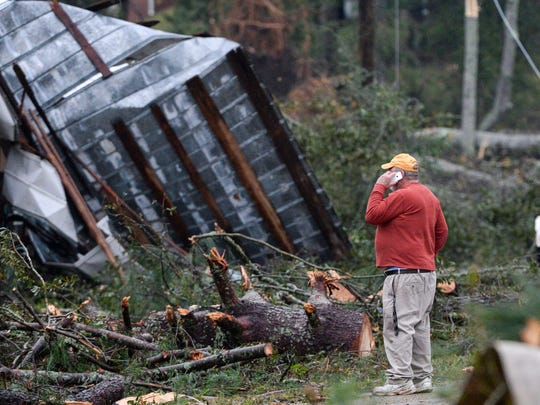 C.B. Gaines talks on the phone while looking at his damaged store along Robinson Bridge Road in Liberty early Monday.