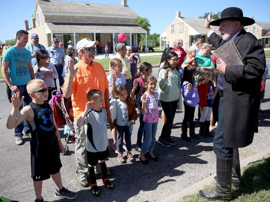 Jack Smith, also known as Cactus Jack in the Concho Cowboy Company, deputizes children after a skit during the Fort Concho Frontier Day in 2016.