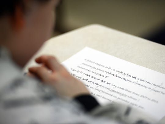 A middle school level student works on his writing