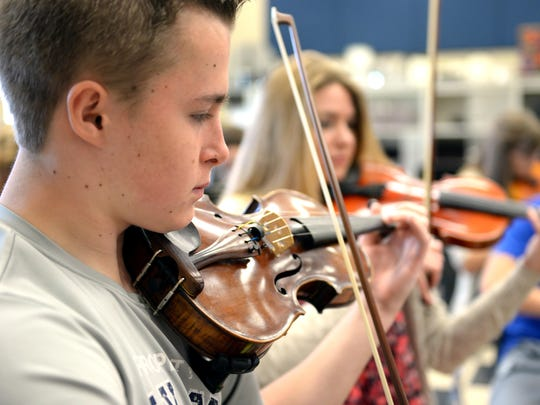 Isaac Geiken, left, and Becca Kornowski play in the Bay Port High School orchestra rehearsal earlier this month. Participation in Bay Port's music program has jumped, reversing a slump in recent years.