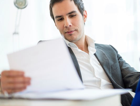 Businessman Reviewing Documents at his Table