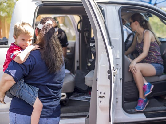 Aiden Klein, 5, waits with his grandmother as his mother, April Klein, right, learns how to properly install his car seat into her truck.