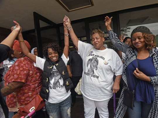 Casche Alford was arraigned Friday in the January murder of 13-year-old Nate Plummer. Family friend Lisa Taylor Hardwick, Nate's grandmother, Darlene Adderly, and his great-aunt, Madeline Adderly, raise their arms outside the courthouse.